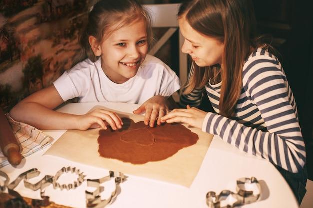 テーブルで家庭の台所で美しい女の子が生地からハート型のクッキーを切り取る Premium写真
