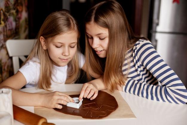 テーブルの家庭の台所で幸せな姉妹は、生地からハート型のクッキーを切り取った Premium写真