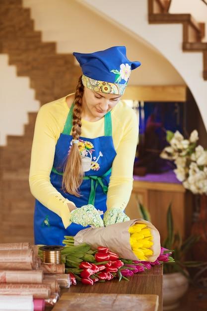Девушка-флорист упаковывает красивые тюльпаны в цветочный магазин в крафт-бумаге Premium Фотографии