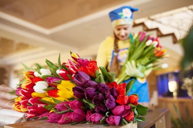 女の子の花屋はクラフトペーパーのフラワーショップで美しいチューリップを梱包します。 Premium写真