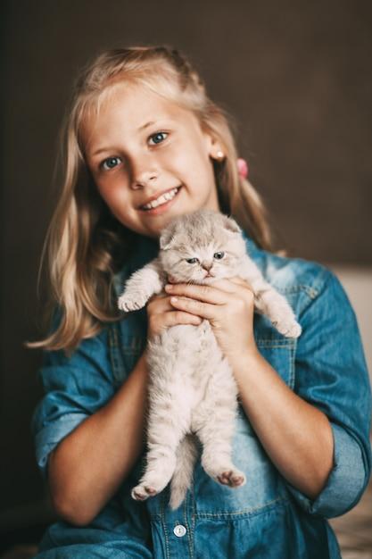 Девочка обнимает британского маленького котенка Premium Фотографии