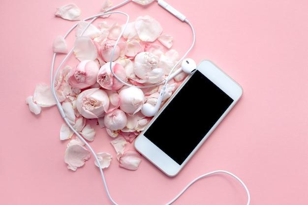 Белый телефон и наушники лежат на нежных розах и лепестках на розовом фоне Premium Фотографии