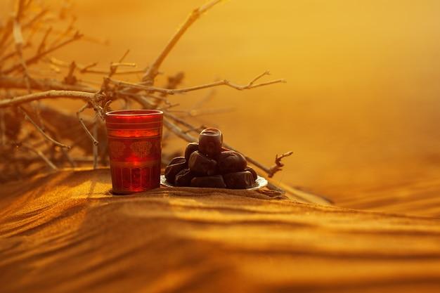 美しい夕日を見下ろす砂の上に、コップ一杯の水とデートがあります。 Premium写真