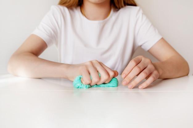 Девушка сжимает голубую слизь рукой Premium Фотографии