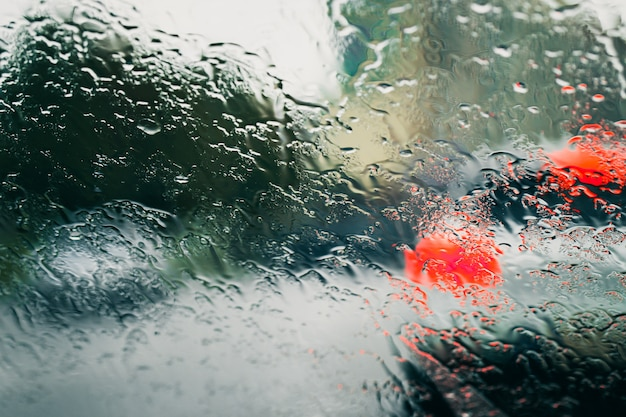 Городская дорога сквозь капли дождя на лобовом стекле автомобиля Premium Фотографии
