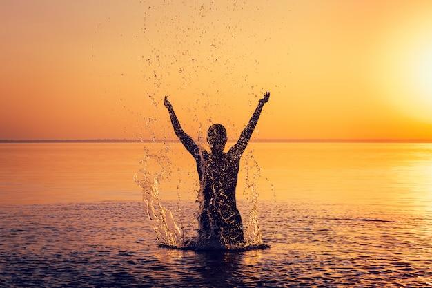 夕暮れ時の穏やかな水で男のシルエット Premium写真