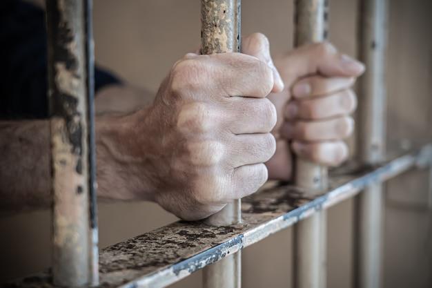 Крупным планом руки заключенного в тюрьме Premium Фотографии
