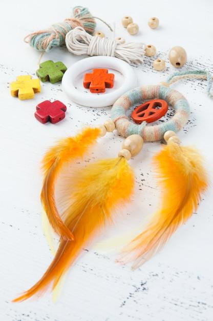 オレンジ色のピースサインと明るいドリームキャッチャー Premium写真