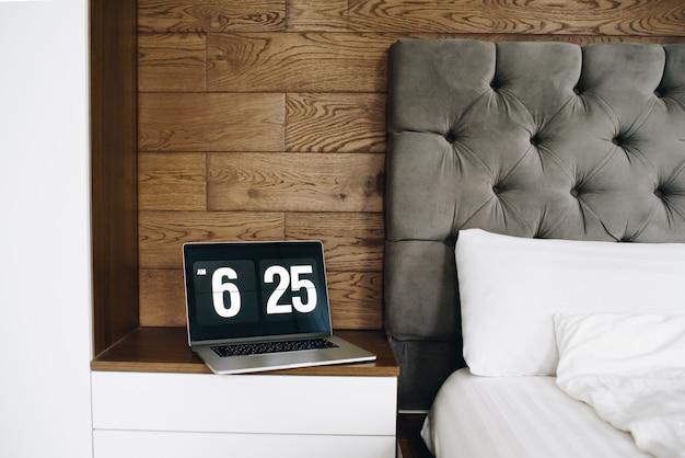 Ноутбук с часами возле кровати, работая дома рано утром Premium Фотографии