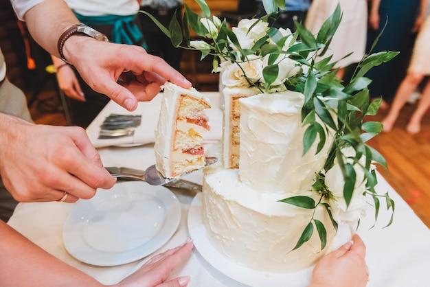 葉で飾られた美しいウェディングケーキを切る新郎新婦 Premium写真