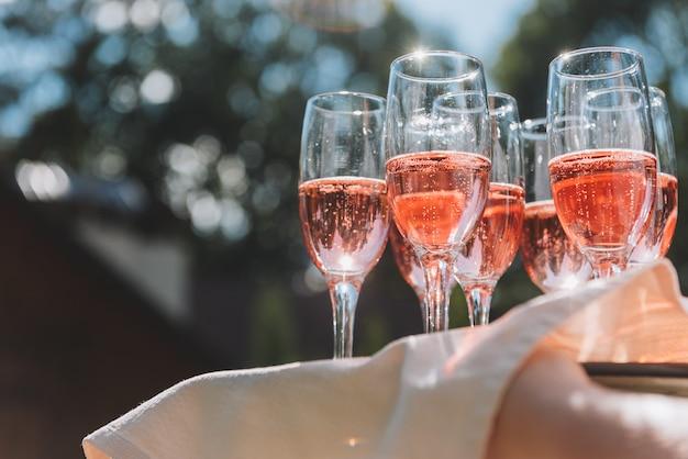 Поднос с бокалами летнего розового игристого вина для гостей на свадебном приеме в солнечных лучах Premium Фотографии