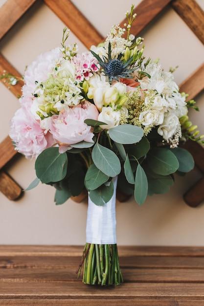 バラ、シャクヤク、ユーカリの葉を持つモダンでエレガントな花嫁のブーケ Premium写真