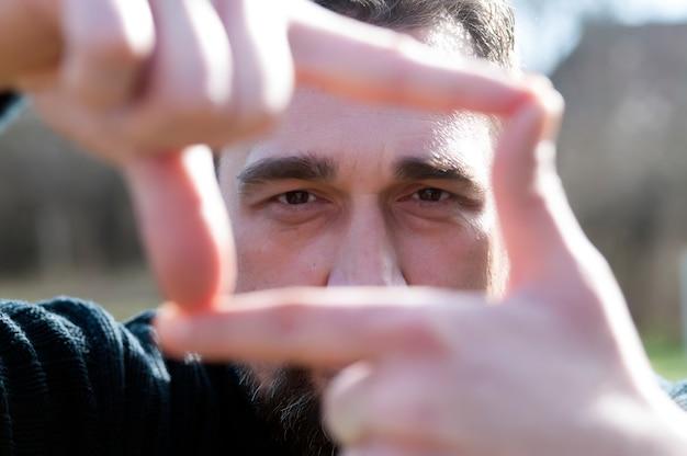 Закройте великолепный бизнесмен, глядя на камеру, делая жест рук. Premium Фотографии
