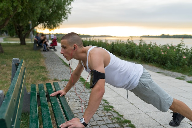屋外腕立て伏せをしている若い男 Premium写真