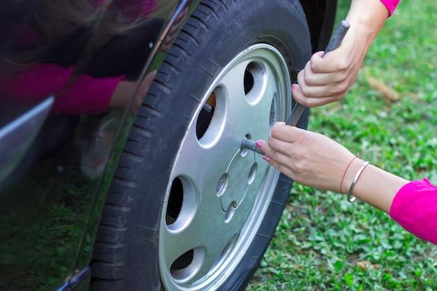 彼女の車にタイヤを変更する女性 Premium写真