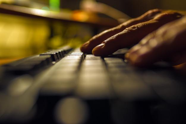 暗闇の中でコンピューターのキーボードを押す指。 Premium写真