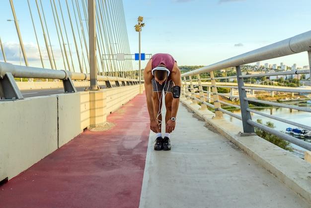 彼の足を伸ばして男性ランナー。 Premium写真
