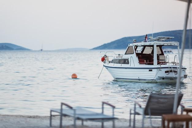 ビーチ近くに立っている美しいターコイズブルーの海でクロアチアの旗と白いヨット Premium写真