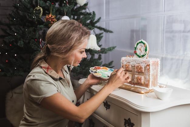 女性は自宅でジンジャークッキークリスマスのチェストを飾ります。女性は蜂蜜のジンジャーブレッドクッキーに塗料を描画します Premium写真