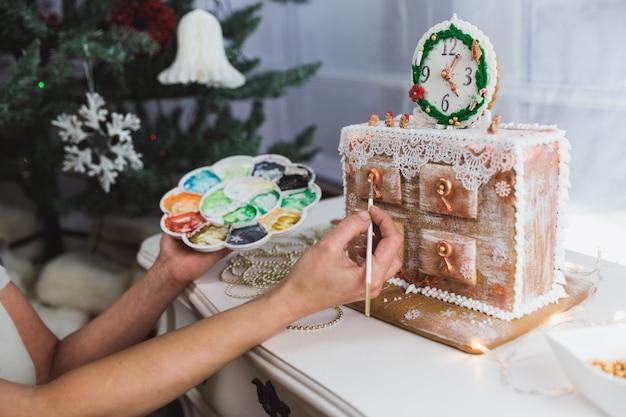 Женщины украшают имбирное печенье рождественским комодом в домашних условиях. женщина рисует краски на пряники. крупный план Premium Фотографии