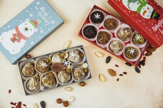 Вкусные органические домашние порционные сырые конфеты сложены в подарочные рождественские коробки Premium Фотографии