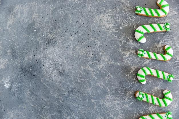Ручная роспись рождественские пряники зеленые и белые конфеты тростника на красивом сером фоне. Premium Фотографии