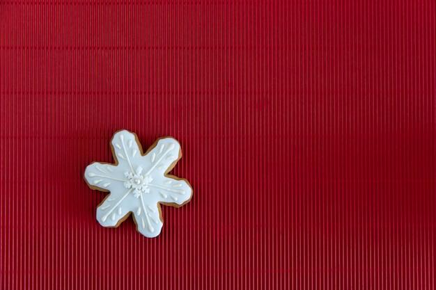 手描きの赤い波状の背景にクリスマスジンジャーブレッド白いスノーフレーク。カードのコンセプト。上面図。平干し。 Premium写真