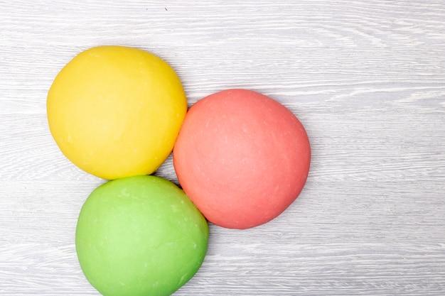 Три красочных красного, зеленого и желтого теста на столе Premium Фотографии