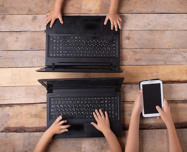 ラップトップとタブレットをつなぐ子どもたち Premium写真
