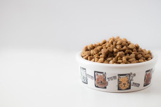 白い背景の上の白いボウルに猫や犬のための乾燥食品。 Premium写真
