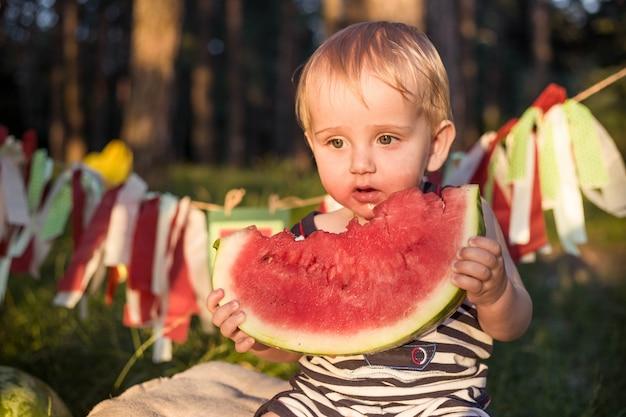 金髪の少年は健康的な食習慣を持っています Premium写真