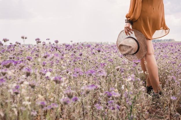 ほっそりした足。麦わら帽子をかざす少女の手 Premium写真