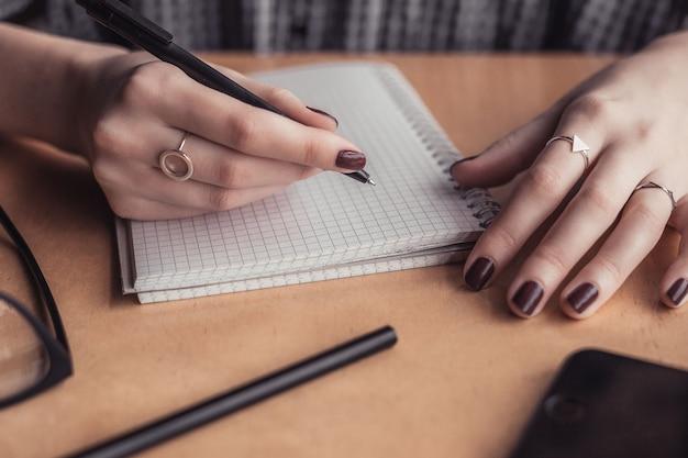 コーヒーショップの木製テーブルに女性手書くメモ帳 Premium写真