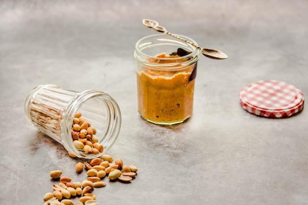灰色のテーブルの上の瓶の中のクリーミーで滑らかなピーナッツバター。 Premium写真