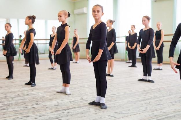 子供たちは広いトレーニングルームでトレーナーと踊ります。 Premium写真