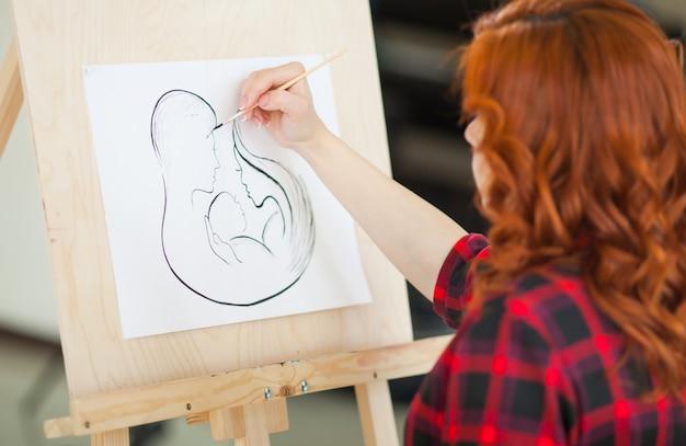 妊娠中の女の子は彼女の将来の家族の絵を描きます。 Premium写真