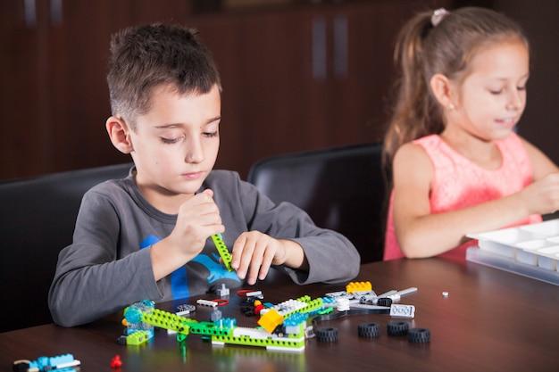 陽気な笑顔の子供たちがコンストラクターを構築しています。 Premium写真