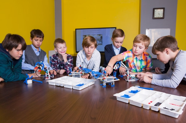 Позитивные дети играют и собирают конструктора в детской комнате. Premium Фотографии