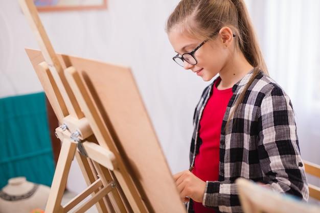 子どもたちは美術学校でイーゼルに絵を描きます。 Premium写真