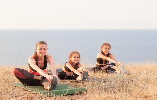 インストラクターは、海の山でヨガの子供たちを訓練します。 Premium写真