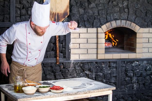 レストランでピザを準備する料理。 Premium写真