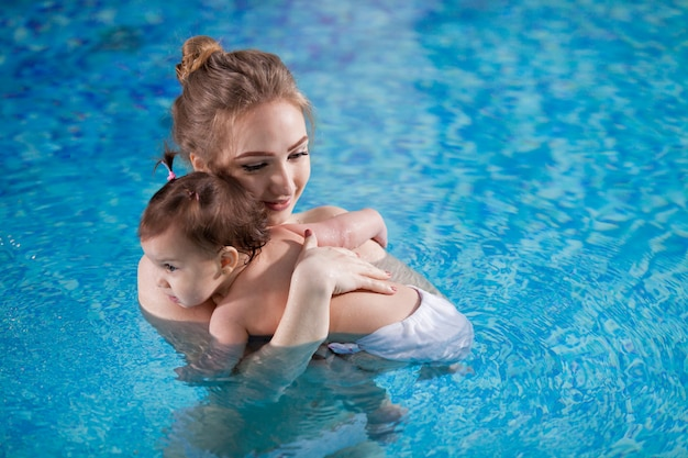 若い母親は、プールで赤ちゃんを浴びます。 Premium写真