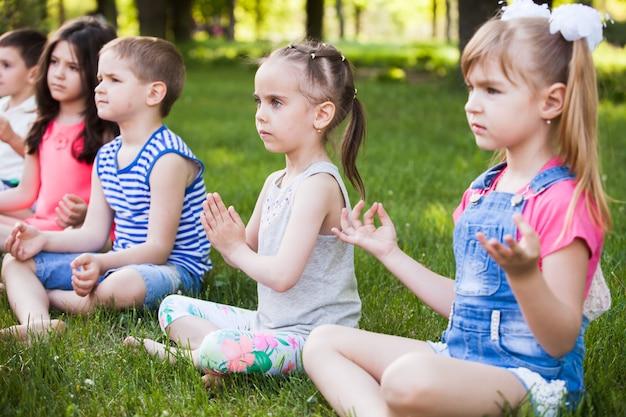 ヨガを練習する子供たち。 Premium写真