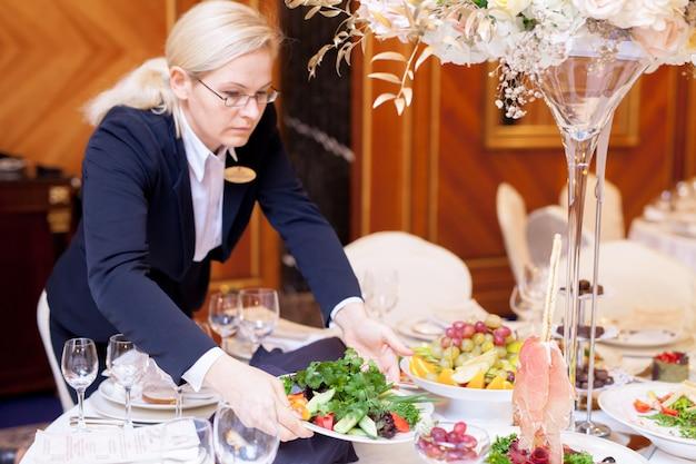 ウェイターはレストランで宴会のテーブルを設定します Premium写真