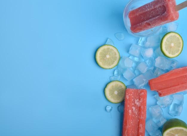 アイスキャンデーと青い背景にレモン 無料写真