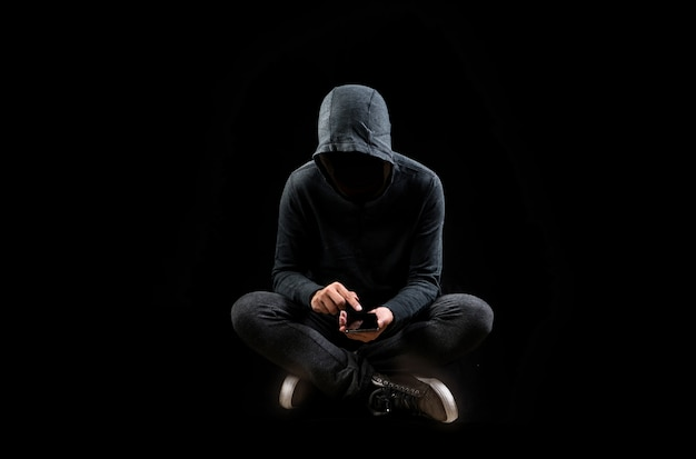 携帯電話のスマートフォンでデータを盗むコンピューターハッカー Premium写真