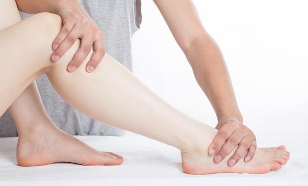 足裏マッサージをしている女性の手のクローズアップ Premium写真