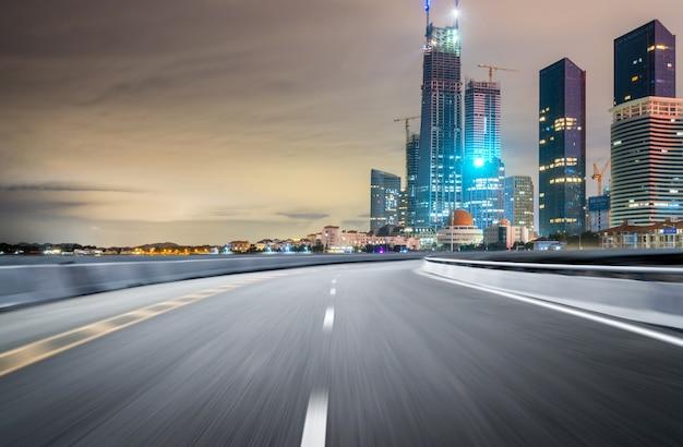 Пустое шоссе с городским пейзажем и горизонтом циндао, китая. Premium Фотографии