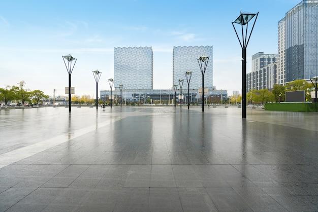 パノラマスカイラインと空のコンクリートの正方形の床の建物 Premium写真
