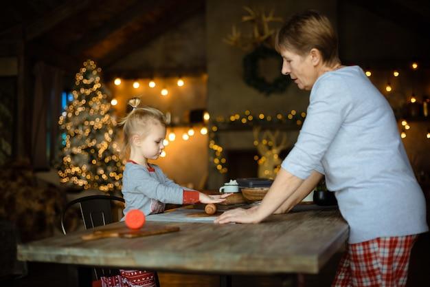 若い祖母と彼女の素敵な金髪の孫娘は、クリスマスの装飾が施された家で一緒にクッキーを作ります。 Premium写真